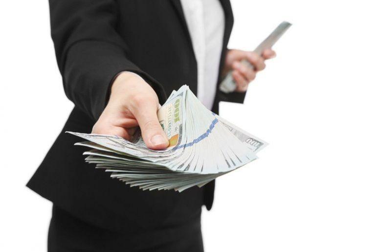 Woman in black suit offering money