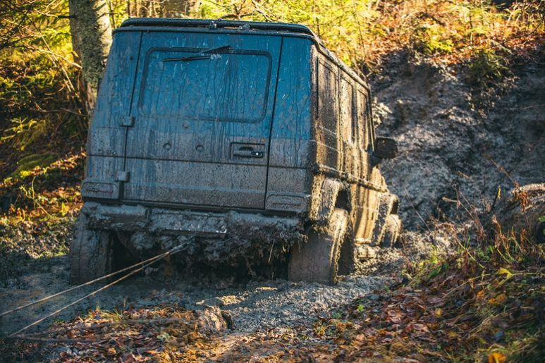 Dirty offroad car stuck in dirt on sunny autumn day.
